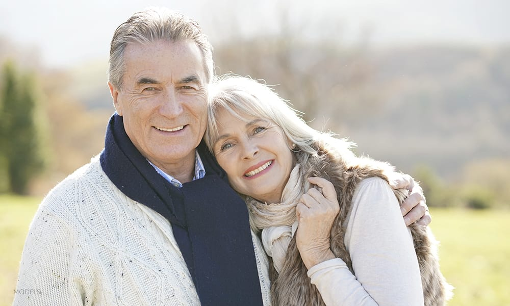 Mature Caucasian Couple In Winter Clothing Cuddling Outdoors