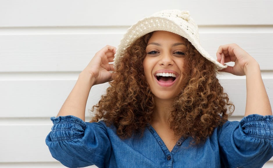 African American Woman Smiling Holding Crochet Sun Hat With White Wood Paneling In Background