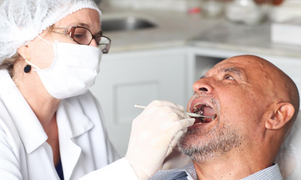 Dentist Examining Male Patient